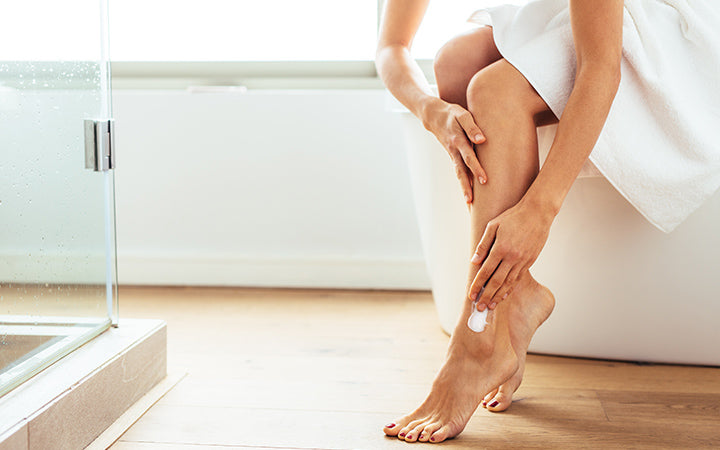 woman applying moisturizer to her legs after bath