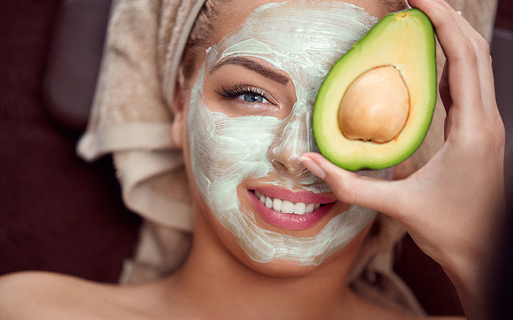 woman applying natural avocado mask on her face