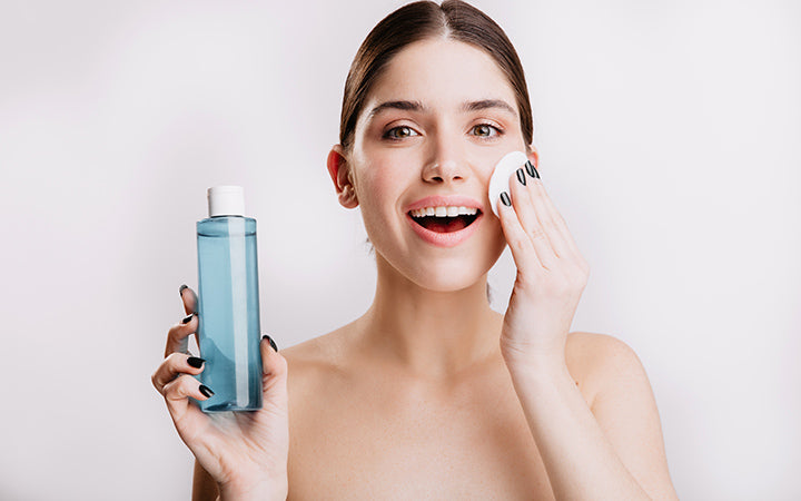 woman delicately moisturizes skin with cosmetic tonic