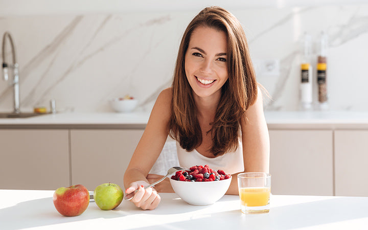 woman eating fresh berries from a bowl