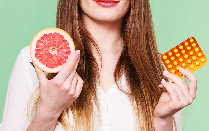 woman holding pills and grapefruit in two hands