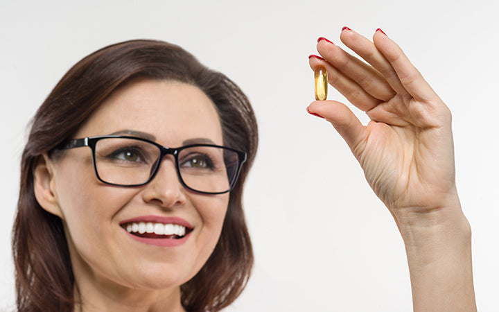 woman holds a capsule with vitamin e