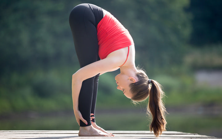 woman performing Uttanasana pose