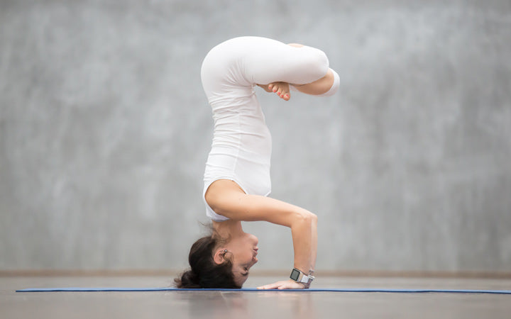 woman performing handstand with padmasana legs
