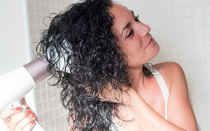 woman using hair dryer on curly hair