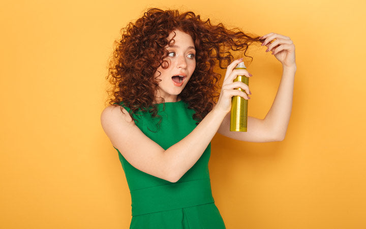 woman using hair spray on curly hair