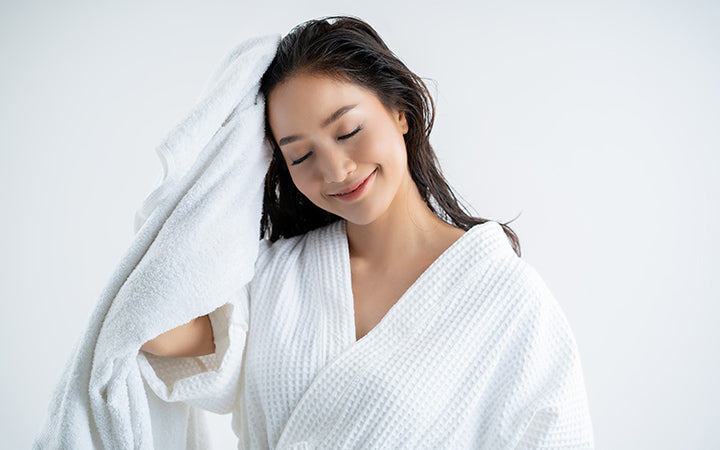 woman using towel to dry hair