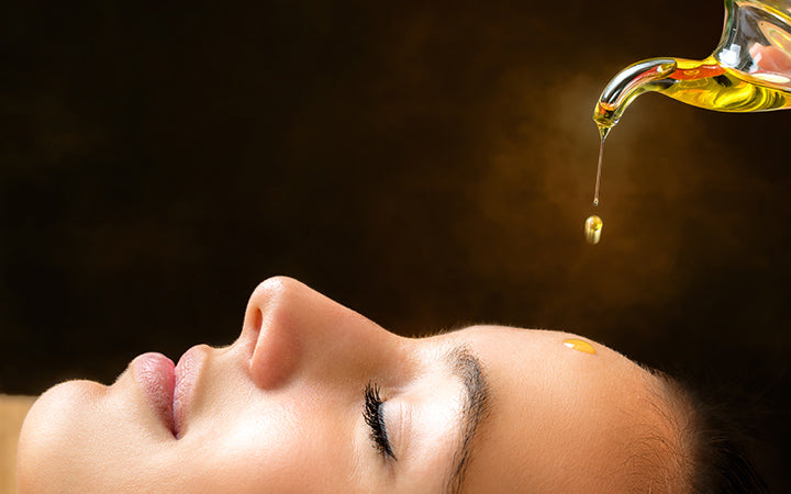 woman with ayurvedic oil dipping on face