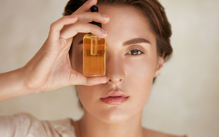 woman with bottle of essential oil