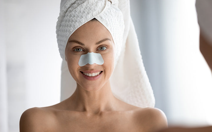woman with cleansing facial strip on nose
