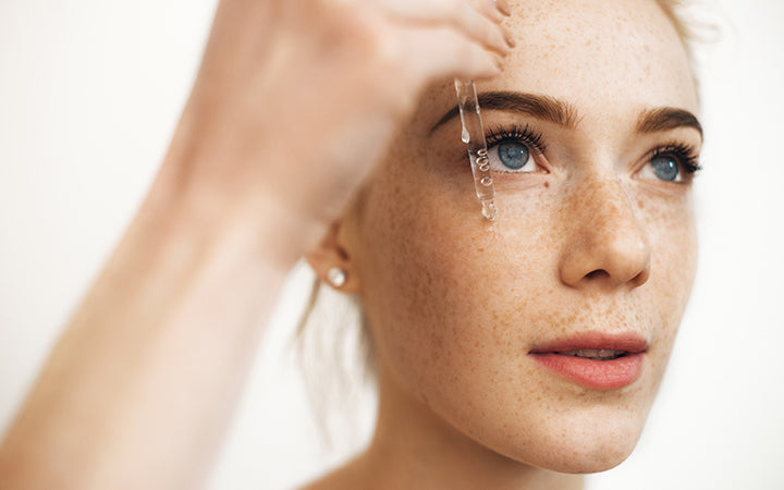 woman with freckles applying essential oils