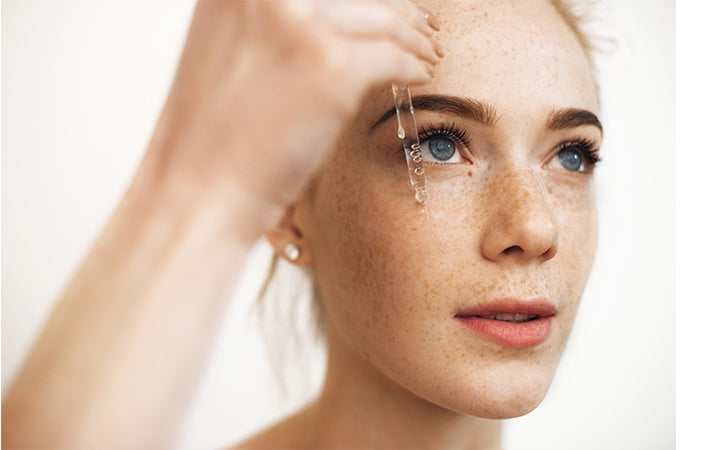 woman with freckles applying serum