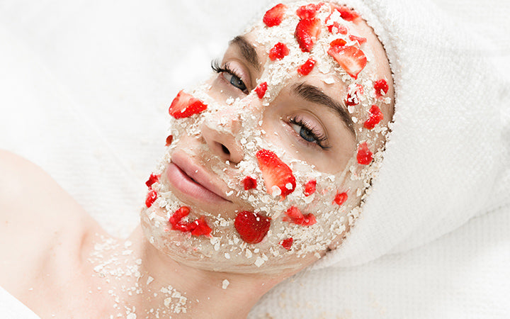 woman with oatmeal & strawberry mask on her face