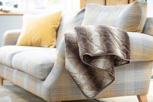 collared Creatures Luxury Dog Blanket -Sofa Throw In Brown Faux Fur displayed on a modern grey check sofa