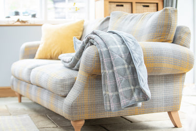 Luxury Dog Blanket -Sofa Throw in a modern grey check with hints of beige and pink displayed on a modern grey check sofa