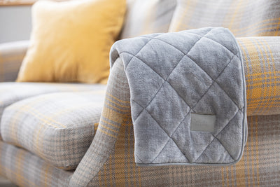 collared Creatures Luxury quilted Dog Blanket -Sofa Throw In Grey Faux Fur displayed on a modern grey check sofa