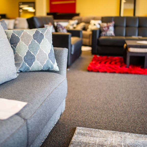 asy furniture showroom  gray sofa with pillows and red rug