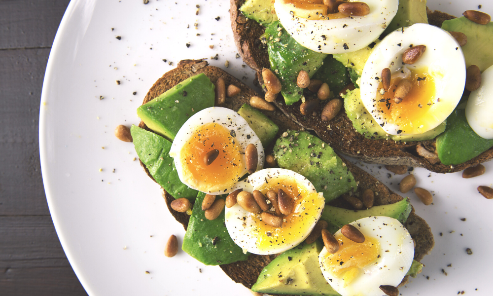 poached egg on smashed avocado toast with roasted pine nuts is a great meal for breastfeeding mums