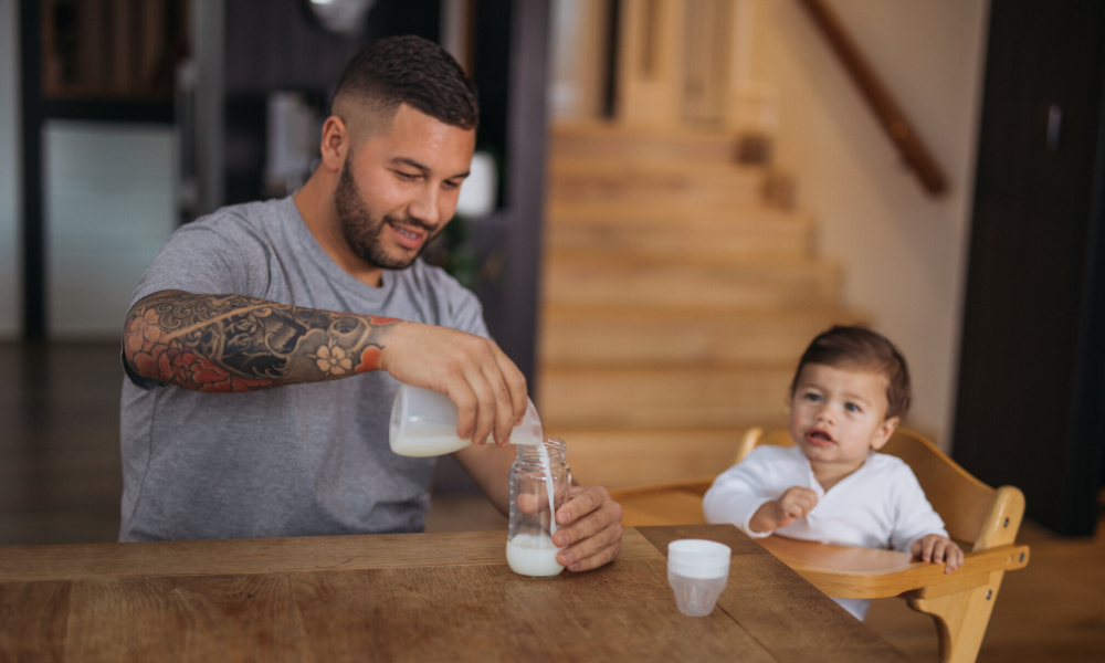 Tattooed Dad is pouring breast milk from Pumpd silicone breast pump into baby bottle to feed to his son