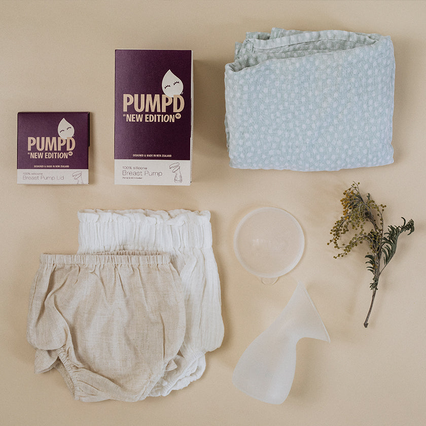 flatlay image of the Pumpd Breast Pump next to baby clothes and baby blanket
