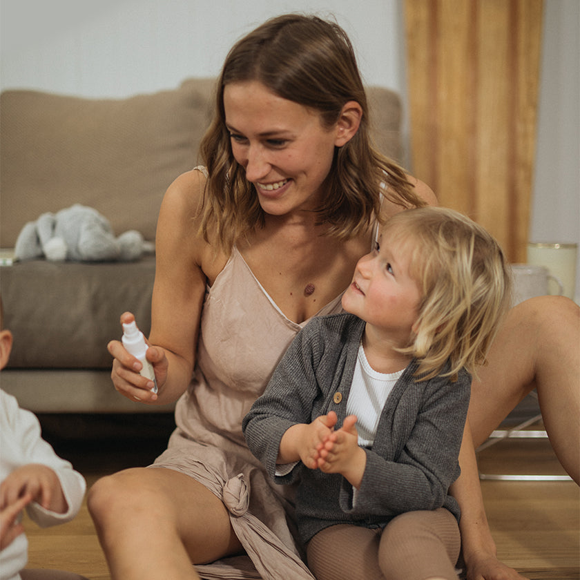young mum sitting on floor with her two sons holding the baby hand sanitiser spray