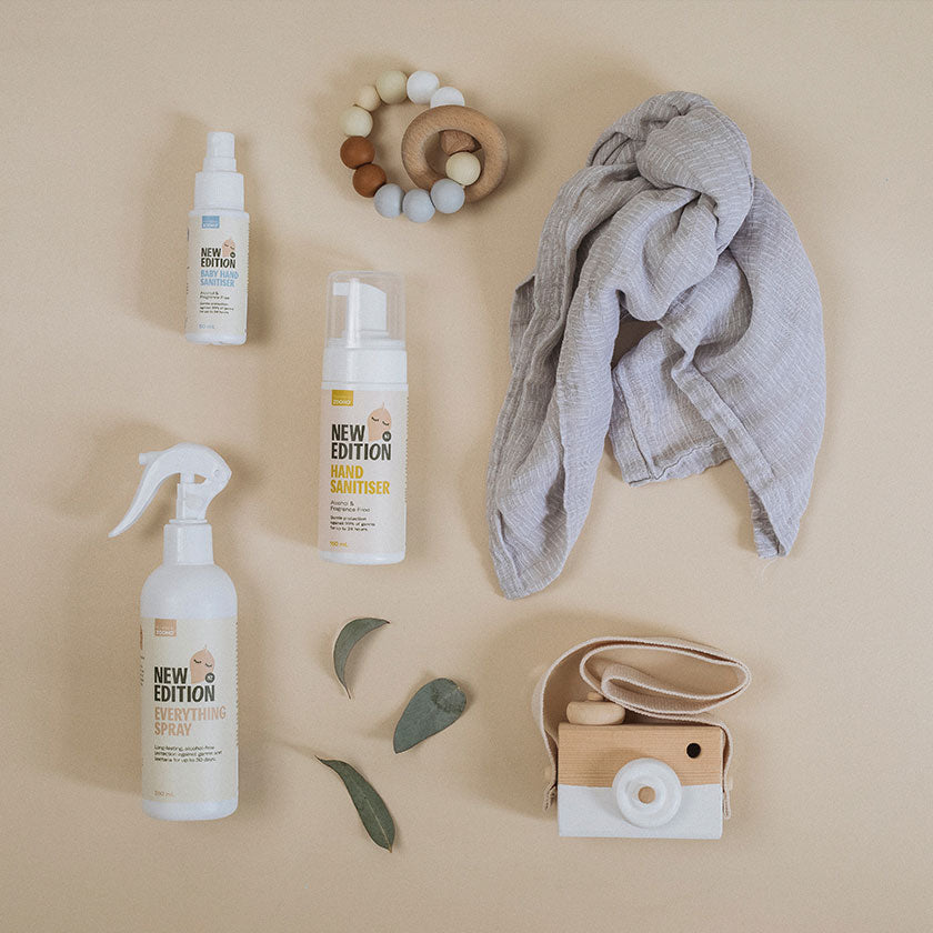 Flat lay image of the sanitiser range accompanies by a baby teething toy, muslin cloth, toy camera and olive leaves