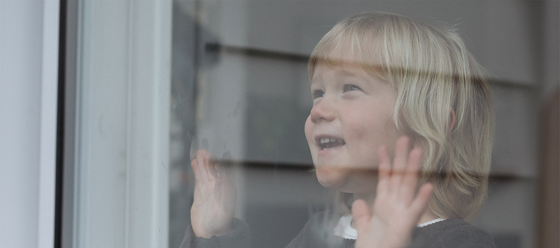 photo of young boy looking through the window with his hands on the glass smiling