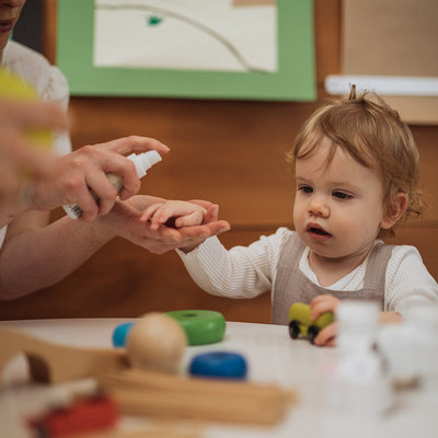 mum holding baby girls hand to spray it with the New Edition Baby Hand Sanitiser, while she plays with colourful blocks
