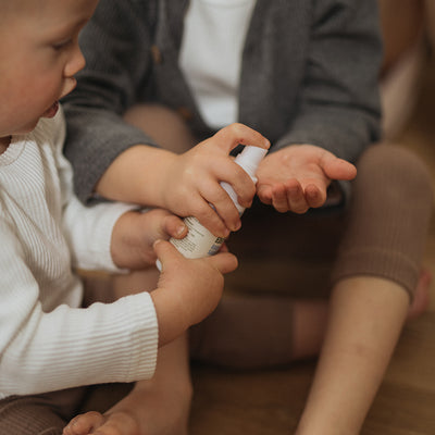 Baby and toddler using the baby hand sanitiser spray to kill germs and protect