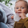 teething toddler is looking at the camera and using the soft Pumpd breast pump lid to chew on