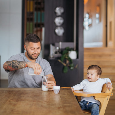 tattooed dad sitting at dining table pouring expressed breast milk into baby bottle from the Pumpd soft silicone breast pump while baby boy sits next to him in high chair smiling