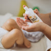 Mum using Alcohol Free Hand Sanitiser to clean hands after changing dirty baby nappy