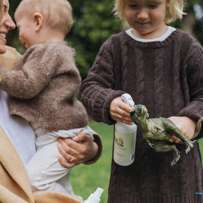 Mum holding baby while her other son uses the Everything Spray to clean his toy dinosaur