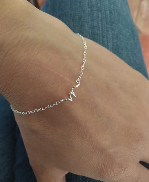 twised style trace chain sterling silver bracelet being worn