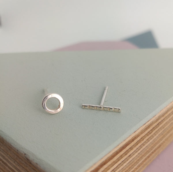 detail of circular and bar shaped asymmetric stud earrings in sterling silver
