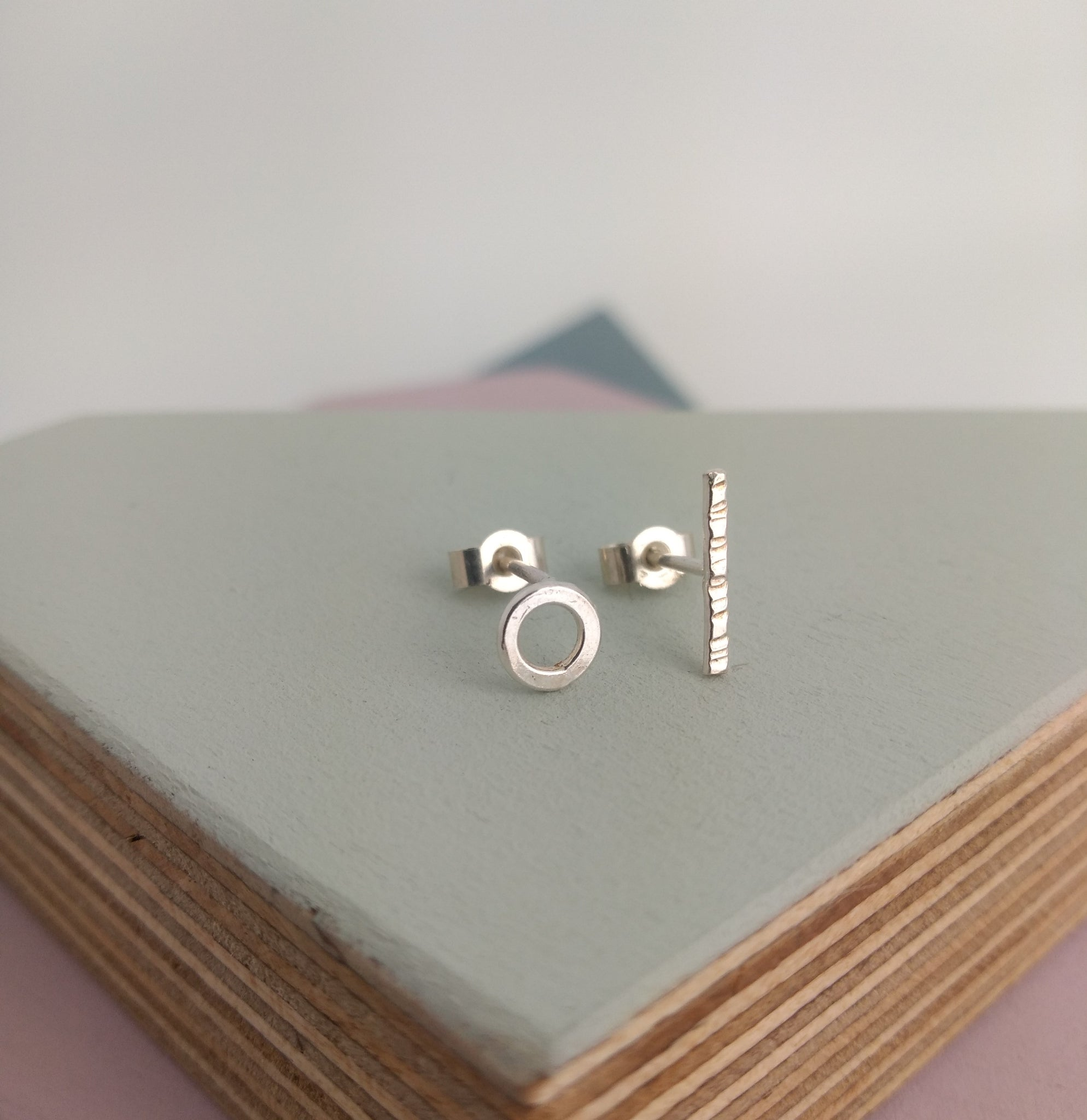 small mis-matched stud earrings in sterling silver one circular one bar textured style
