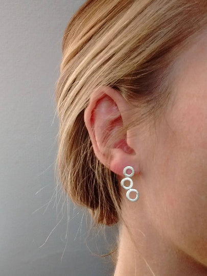 Sterling silver concentric circle drop style earrings being worn on the earlobe