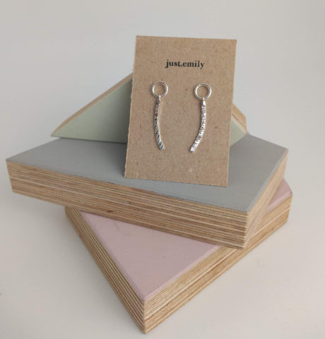 circle and textured linear drop dangly earrings on kraft card display