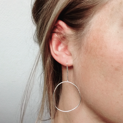 organic shaped circular wire earrings in sterling silver displayed being worn