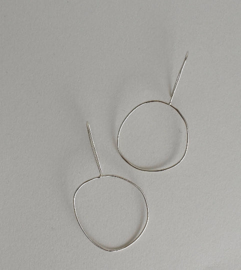 organic circular shaped drop earrings in sterling silver wire displayed on white background