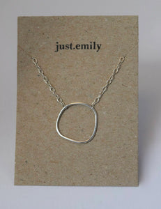 organic unique pebble inspired necklace with sterling silver wire design on trace chain displayed on kraft card.