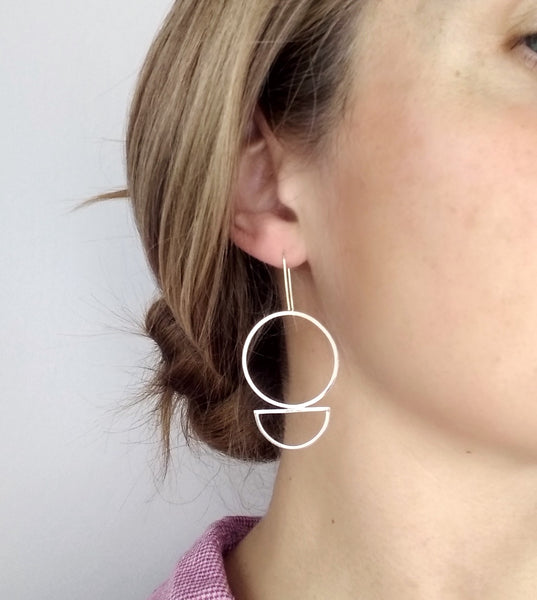 large statement geometric earrings with circle and semi circle shapes being worn