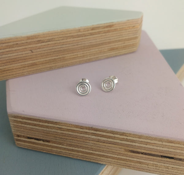 simple geometric stud earrings with circular aztec inca design displayed with butterfly scroll backs