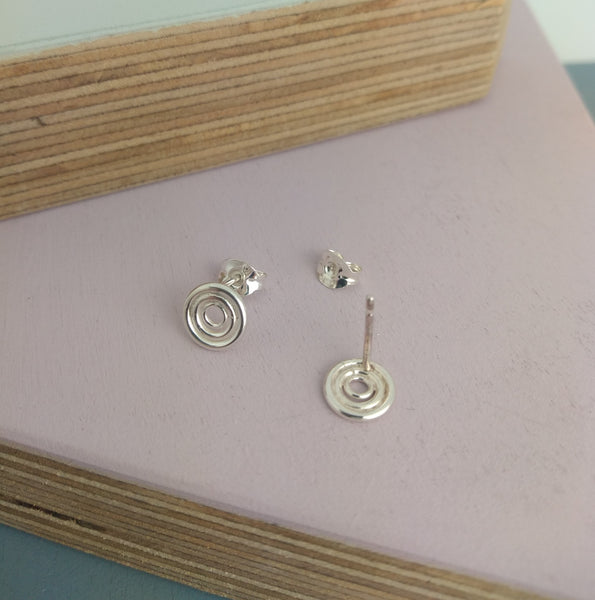 circular stud earrings one displayed on the back with pin visible