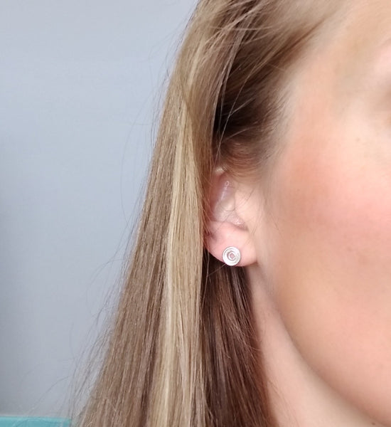 sterling silver circular stud earrings being worn on the earlobe