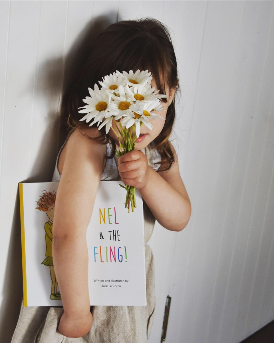 Little girl holding her favourite book hiding behind some daisies.