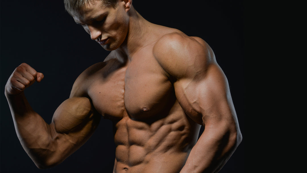 man flexing muscles dark background