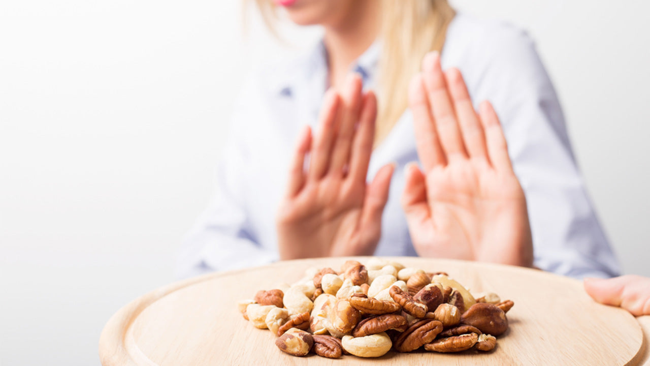 woman rejecting a plate of peanuts