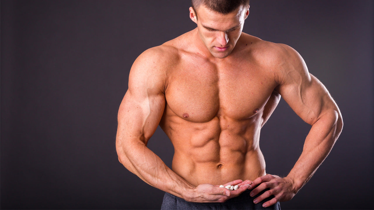 man with big muscles with a handful of capsules