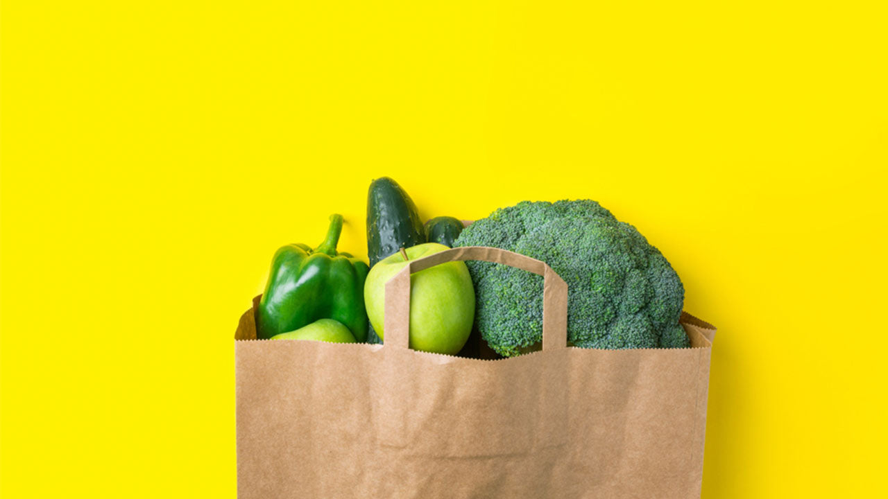 green apple broccoli bell pepper and cucumber in a brown bag
